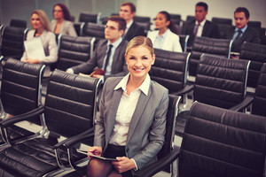 Image Of Business People Sitting In Rows At Seminar With Pretty Woman In Front