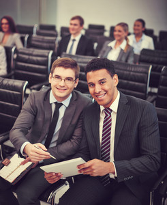 Two Happy Young Businessmen Looking At Camera At Seminar On Background Of Their Colleagues