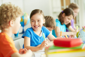 Portrait Of Happy Pupil Looking At Her Classmate At Lesson