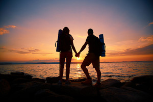 Image Of Beautiful Scene Of Sunset And Backs Of Couple Of Hikers Enjoying It