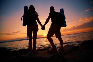 Image Of Beautiful Scene Of Sunset And Backs Of Couple Of Hikers Enjoying It