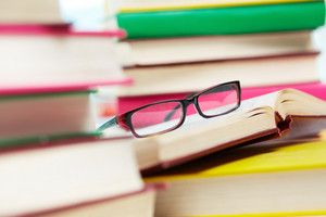 Close-up Image Of Eyeglasses Among Piles Of Books