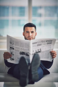 A Young Businessman Sitting On Sofa And Reading Newspaper