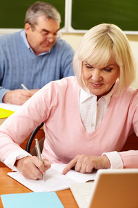 Portrait Of Blond Female Making Notes In Copybook With Senior Man On Background