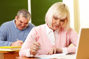 Portrait Of Mature Female Making Notes In Copybook With Senior Man On Background