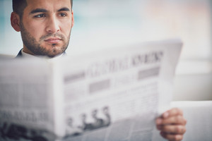 A Young Serious Businessman Reading Newspaper