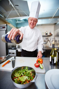 Image Of Male Chef Preparing Vegetable Salad In The Kitchen