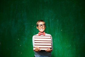 Happy Schoolboy In Eyeglasses Holding Stack Of Books While Standing By The Blackboard And Looking At Camera