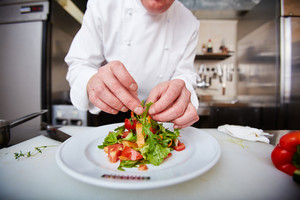 Hands Of Male Chef Serving Vegetable Salad In The Kitchen