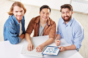 Group Of Successful Businessmen With Laptop Looking At Camera