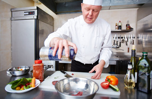 Image Of Male Chef Adding Spices To Meat In Bowl