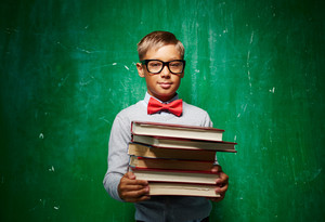 Cute Elementary Pupil In Eyeglasses Holding Textbooks