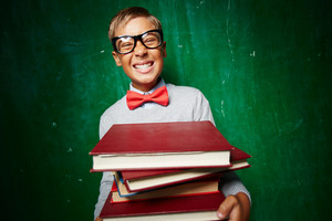 Ecstatic Kid In Eyeglasses Holding Books While Standing By The Blackboard