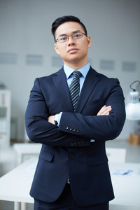 Serious Businessman In Suit Standing In Office
