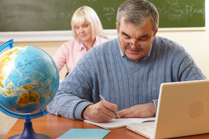 Senior Man Doing Written Task In Classroom