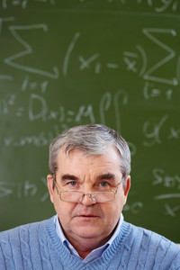 Portrait Of Aged Teacher Looking At Camera With Blackboard On Background