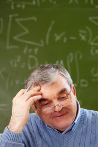 Portrait Of Aged Teacher Thinking Of Idea With Blackboard On Background
