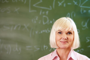 Portrait Of Blond Female Looking At Camera With Blackboard On Background