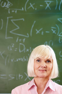 Portrait Of Mature Blond Female Looking At Camera With Blackboard On Background