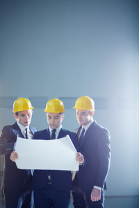 Copy-spaced Image Of A Three Construction Workers Holding A Draft And Discussing Something