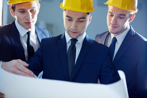 Close-up Of Workers Looking At Blue Print And Planning