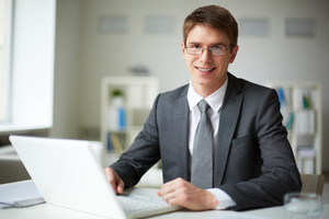 Smiling Businessman In Suit Working With Laptop In Office