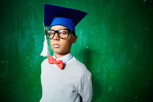 Cute Elementary Pupil In Eyeglasses And Graduation Hat Looking At Camera