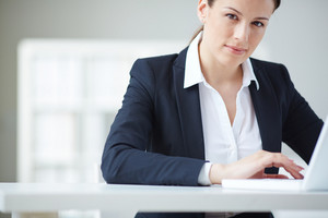 Young Businesswoman Typing And Looking At Camera In Office