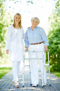 Pretty Carer And Senior Patient Walking Outside