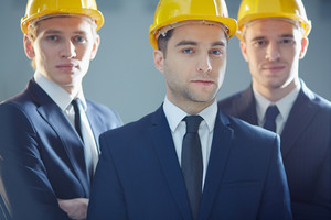 Closeup Portrait Of A Group Of Contractors Posing At Camera With The Leader On The Foreground