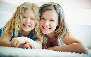 Portrait Of Happy Woman And Her Daughter Lying On The Floor