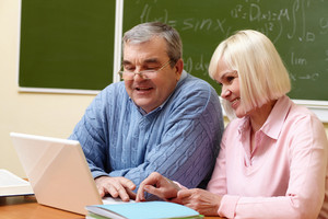 Portrait Of Mature Man And Aged Female Working With Laptop During Training Course