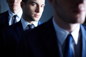Portrait Of An Ambitious Businessman Through His Colleagues On The Foreground