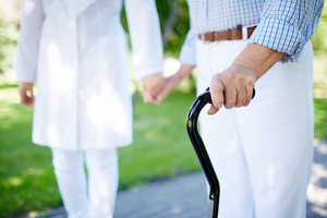 Close-up Of Disabled Female Hand Holding Cane With Her Doctor Walking Near By