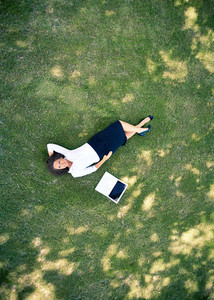 Above View Of Successful Businesswoman Lying On Green Grass With Laptop Near By
