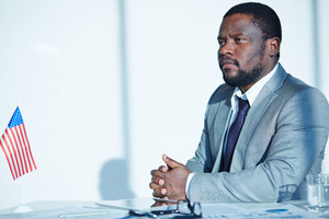 African-american Serious Entrepreneur Sitting At Workplace