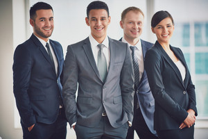 Portrait Of Confident Business Partners Looking At Camera With Male Leader In Front