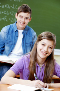 Portrait Of Smart Girl At Workplace With Her Classmate On Background