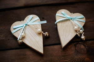 Image Of Wooden Hearts With Blue Ribbons And Pearls On Wooden Background