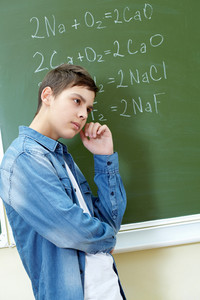 Pensive Boy Standing By Blackboard And Thinking Of Formulae On It