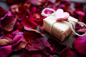 Image Of Valentine Giftbox With Small Pink Heart Surrounded By Rose Petals