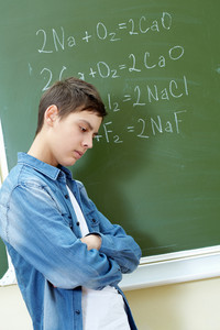 Sad Guy Standing By The Blackboard With Chemical Formulae On It
