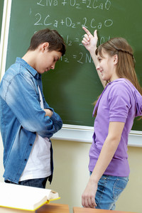 Clever Girl Pointing At Blackboard While Explaining Formula To Classmate