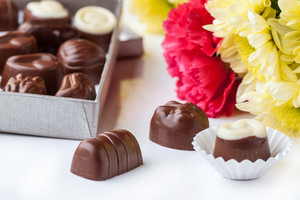Chocolate Candy And Flowers Over White