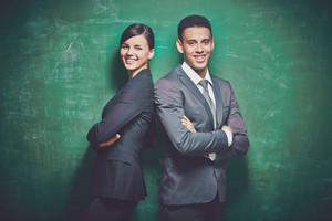 Two Elegant Business Partners Looking At Camera On Green Background