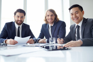 Portrait Of Three Partners At Meeting Table
