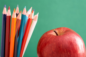 Close-up Of Colorful Pencils With Big Red Apple Near By