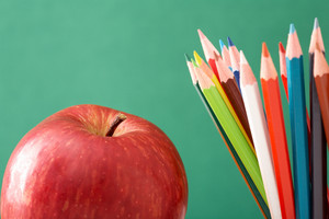 Close-up Of Colorful Pencils With Red Apple Near By