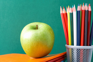 Image Of Crayons And Green Apple Against Blackboard
