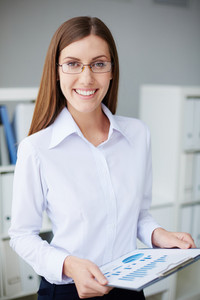 Young Businesswoman With Document Looking At Camera In Office